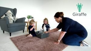 Nurse and 2 children sitting on rug in living space using a bubble PEP